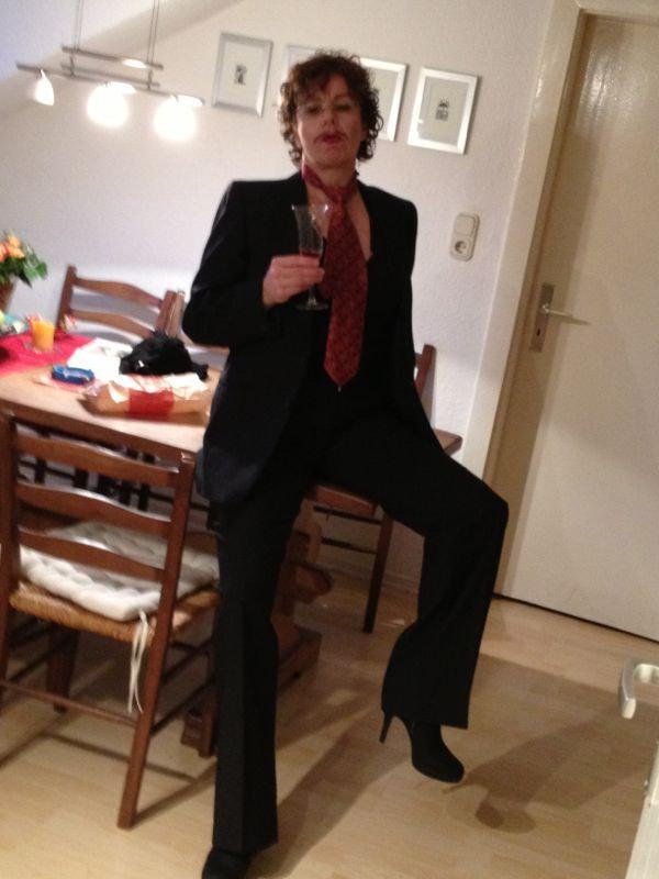Susanne Böhling in männlicher Pose auf dem Tisch sitzend