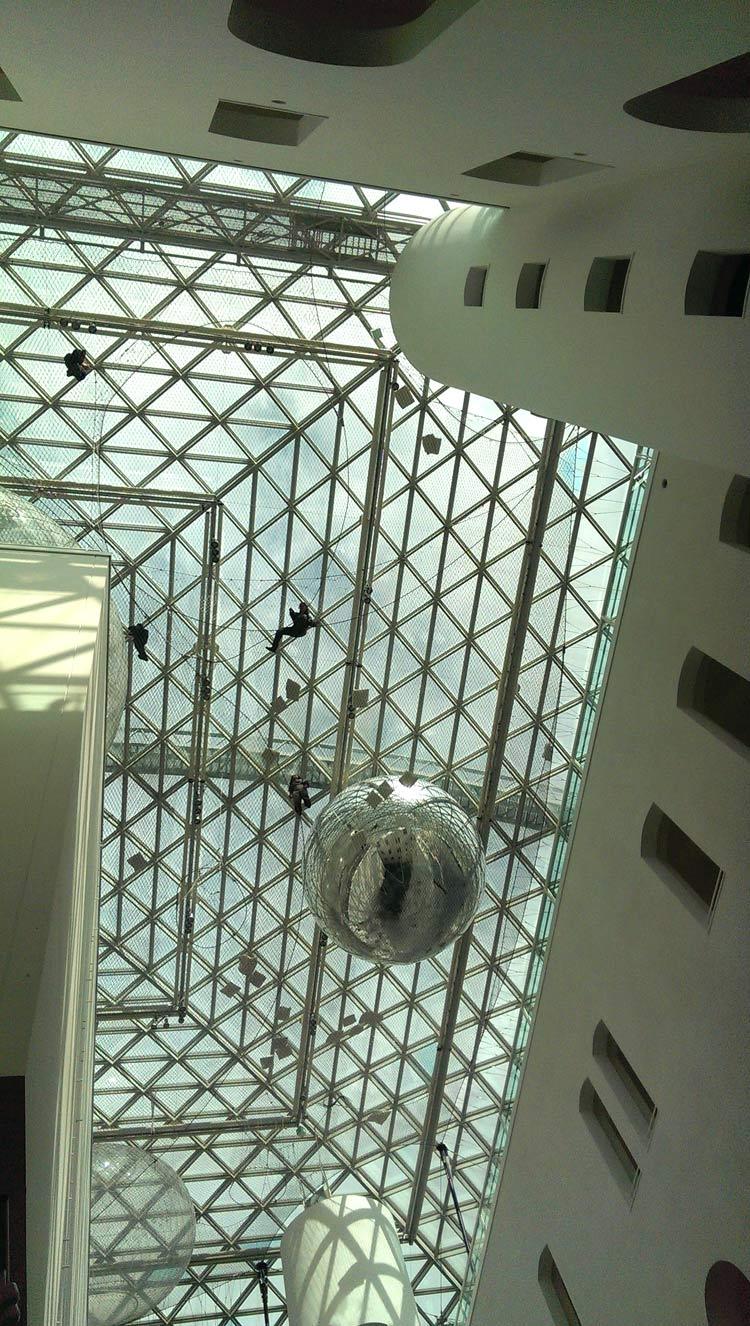 """schon von unten sieht """"in Orbit"""" von Tomás Saraceno atemberaubend aus. Die Menschen auf dem Stahlnetz erscheinen klein wie Fliegen"""