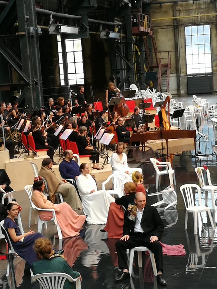 Das Orchester auf dem Podest auf roten Polstern, der Chor auf den Gartenstühlen