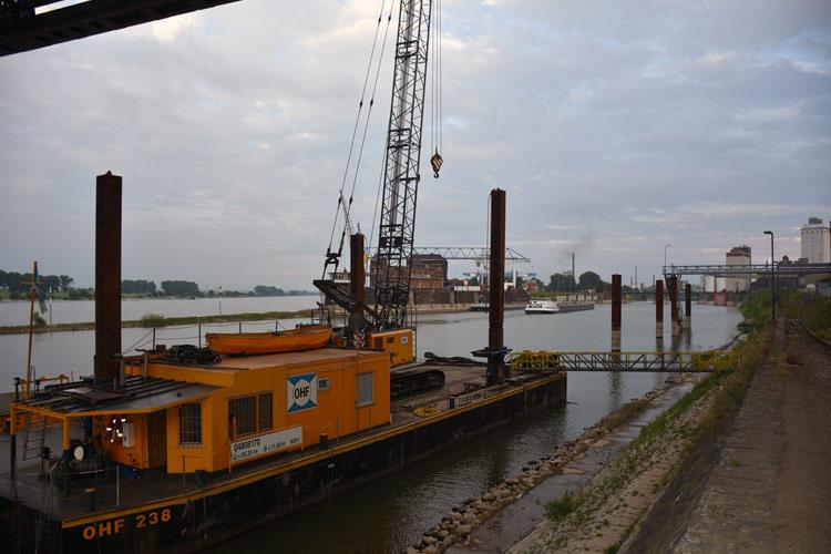 Ein Schiff mit einem Kran liegt unter der Krefelder Rheinbrücke